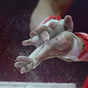A Japanese gymnast  prepares his hands with chalk dust before his horizontal bar routine during the Men's Artistic Gymnastics podium training at North Greenwich Arena during the London 2012 Olympic games preparation at the London Olympics. London, UK. 25th July 2012. Photo Tim Clayton