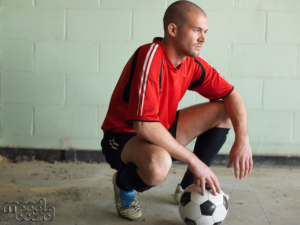 Soccer player crouching with ball side view