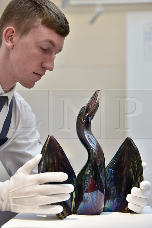 """© Licensed to London News Pictures. 12/10/2017. London, UK.  A technician inspects """"Black Phoenix"""", 2013, by Paul Fryer (Est. GBP3-5k) at a preview of artworks for the """"Art for Grenfell"""" auction taking place at Sotheby's, New Bond Street, on 16 October.  Leading contemporary artists have agreed to donate works to the auction, the proceeds of which will be divided equally amongst the 158 surviving families of the Grenfell Tower fire by the Rugby Portobello Trust charity. Photo credit : Stephen Chung/LNP"""
