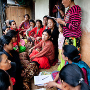 A women's groups discusses topics like micro-finance and personal loans and how to run a farming business along with a family.