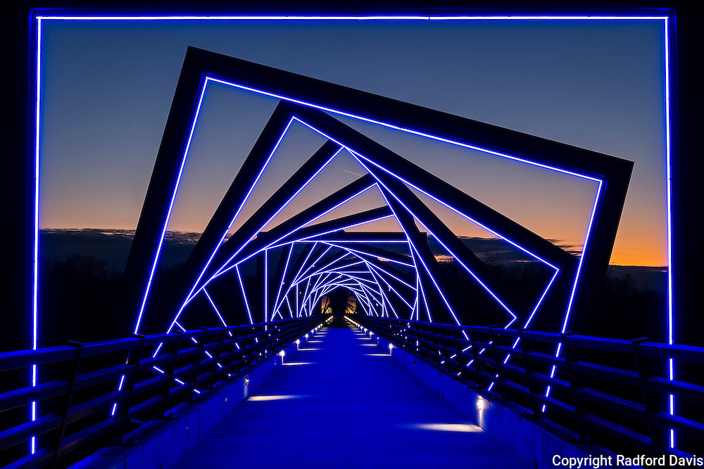 "The High Trestle Trail is a 25 mile long bike path in Iowa, and it includes the High Trestle Bridge, of course. This used to be an active railroad bridge, but the rails have been moved and the bridge is now a biking and walking bridge. The trail is famous for it's 13-story and 1/2 mile long bridge over the Des Moines River, located between Madrid and Woodward in Boone County. At each end of the ½ mile long bridge are four 42' tall artistic towers. The dark bands represent geologic coal veins found in area limestone deposits. There are 41 steel ""frames"" over the bridge represent support cribs within an historic coal mine, which light up blue in the evening. It's a great place for photos. This was taken during a warmer evening last winter. During the summer the bridge is more crowded and it's harder to get a shot like this."