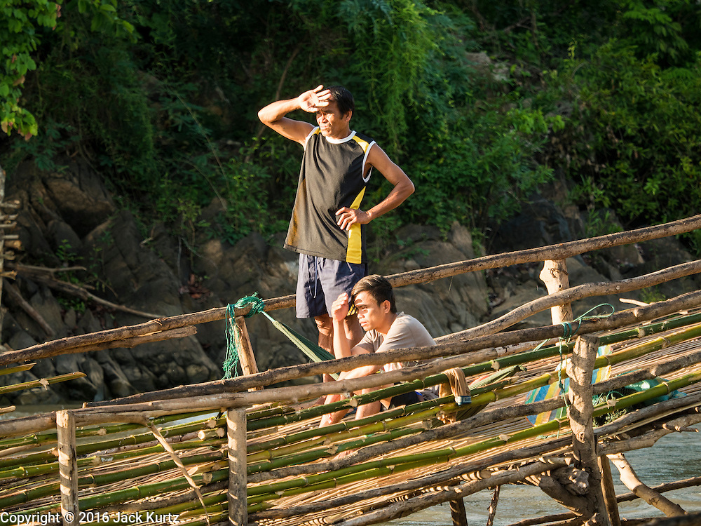 18 JUNE 2016 - DON KHONE, CHAMPASAK, LAOS:  Fisherman in a fish trap look for fish in Khon Pa Soi Waterfalls, on the east side of Don Khon. It's the smaller of the two waterfalls in Don Khon. Fishermen have constructed an elaborate system of rope bridges over the falls they use to get to the fish traps they set. Fishermen in the area are contending with lower yields and smaller fish, threatening their way of life. The Mekong River is one of the most biodiverse and productive rivers on Earth. It is a global hotspot for freshwater fishes: over 1,000 species have been recorded there, second only to the Amazon. The Mekong River is also the most productive inland fishery in the world. The total harvest of fish from the Mekong is approximately 2.5 million metric tons per year. By some estimates the harvest in the Tonle Sap (in Cambodia) had doubled from 1940 to 1995, but the number of people fishing the in the lake has quadrupled, so the harvest per person is cut in half. There is evidence of over fishing in the Mekong - populations of large fish have shrunk and fishermen are bringing in smaller and smaller fish.        PHOTO BY JACK KURTZ