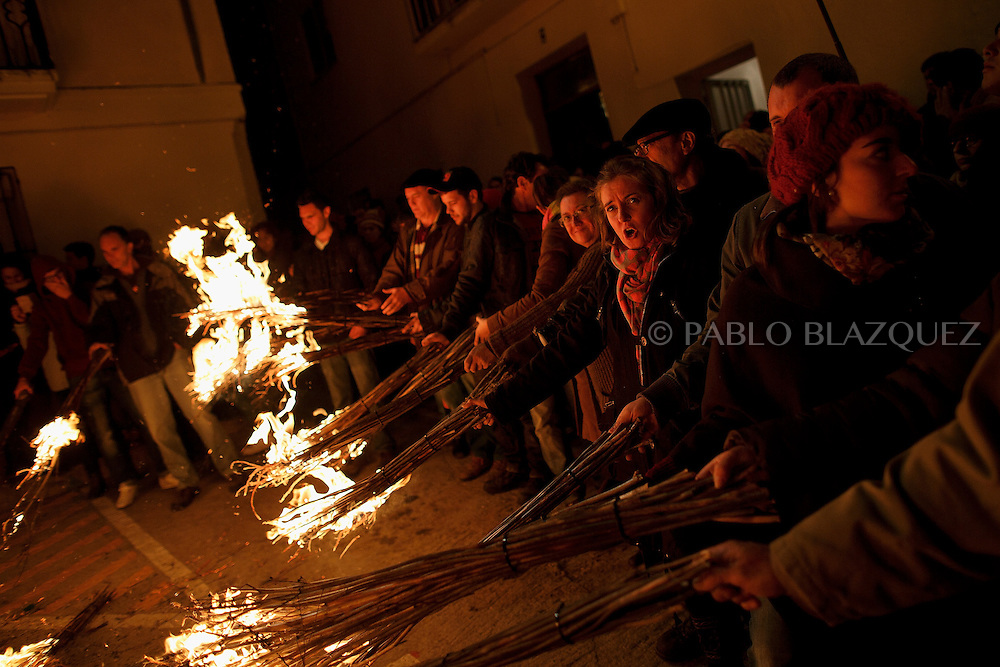 "Revelers hold burning brooms next to a bonfire during the ""La Encamisa"" Festival on December 7,  2014 in Torrejoncillo, Extremadura region, Spain. ""La Encamisa"" is an ancient festival in honor of Immaculate Conception. Hundreds of horsemen wearing a white sheet gather outside the church in the main square. The procession starts when a banner with the image of Immaculate Conception is delivered to the horse rider steward and people cheer and shoot blanks. There are bonfires along the way where people gather to chat, eat traditional sweets and drink local wine. The origin of this tradition is unknown but it is believed the festival comes from a military event in which people from Torrejoncillo were involved. The war in Flanders in 1585, the Battle of Pavia or a legend of the siege suffered by city of Coria. (© Pablo Blazquez)"