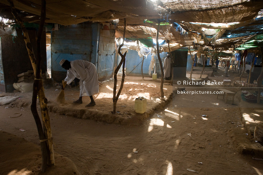 A man sweeps his own area where he sells food in the 4 sq km Abu Shouk refugee camp which is (disputedly) home to 38,000 displaced persons and families on the outskirts of the front-line town of Al Fasher (also spelled, Al-Fashir) in north Darfur.