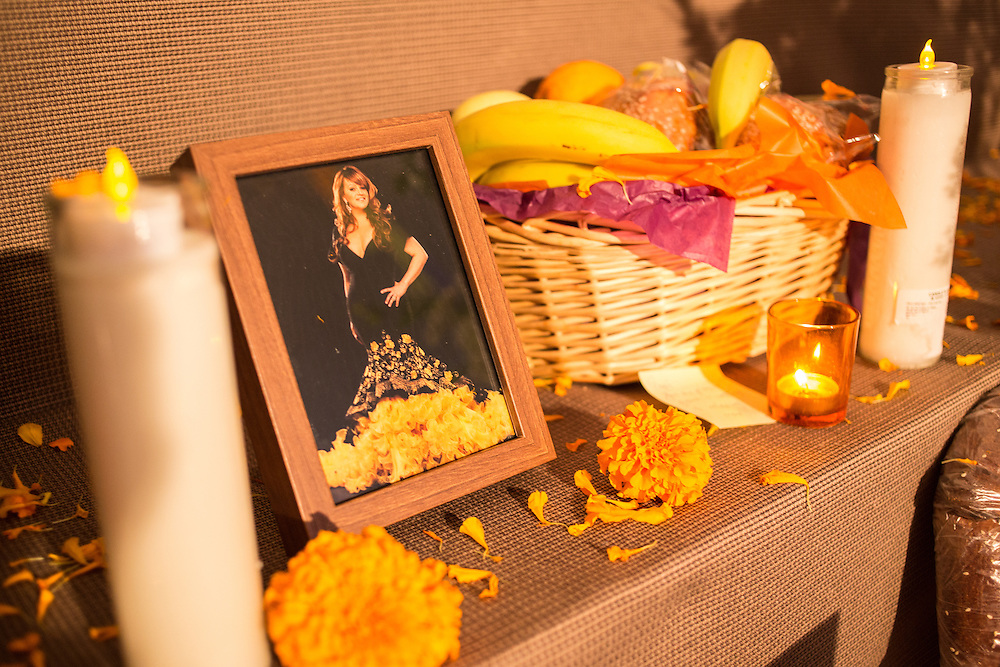 New York, NY, October 31, 2013. A photograph of a woman in a gown is surrounded by orange marigolds, candles, and a basked of bread and fruit.