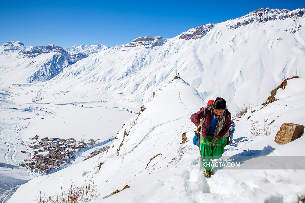 A young school girl climbing the steep ridge above Kaza to reach Komic, a village at 14,500ft. In the winters when the motorable road is  blocked due to snow, this is the only route the locals take to reach the higher villages of Spiti.
