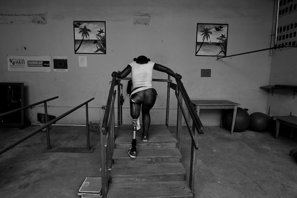 Laissa Christlensa Guerrier, 12 yrs old balances herself as she walks up the stairs during physical therapy at Healing Hands Haiti Clinic. <br /> <br /> Healing Hands Haiti (HHH) in Port Au Prince has been established for 12 years since 1999. Currently, HHH is constructing a new facility in Port Au Prince because their old clinic was destroyed from the earthquake.   HHH provides physical therapy, counseling, prosthetics, and support for free or very little cost to Haitians.  Their funding comes from private donations and organizations such as Handicap International, Mission Europeene Aide Humanitarian, International Committee of the Red Cross (ICRC), American Red Cross, Newman's Own, Direct Relief International (DRI), SOROS Open Society Foundation, and USAID which pays for employees, doctors, supplies, and facilities.  The motto of HHH is &quot;to serve the people of Haiti is to enable them to help themselves.&quot;   Thus, most of their employees are Haitians with very few foreign expats. Furthermore, HHH recruits and teaches young Haitian students prosthetic and orthotic skills and physical therapy in a specialized program that will enable them to earn a degree approved by World Health Organization.
