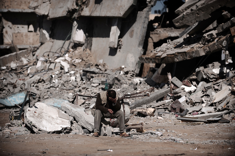A Palestinian man sits in front of buildings destroyed during Israel's 22-day Gaza offensive in Rafah on January 21, 2009, in the south of the Hamas-run territory. Israel and Egypt penned a deal on steps to stem arms smuggling into Gaza ahead of the Jewish state's ceasefire to its war.