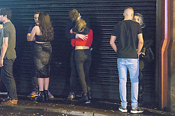 """© Licensed to London News Pictures . 20/12/2014 . Manchester , UK . Clubbers on Bootle Street . """" Mad Friday """" revellers out in the rain and cold in Manchester . Mad Friday is typically the busiest day of the year for emergency services , taking place on the last Friday before Christmas when office Christmas parties and Christmas revellers enjoy a night out .  Photo credit : Joel Goodman/LNP"""