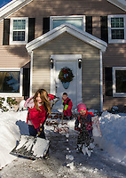Jazmyn, Paul and Aleck Swenson shoveling out their home from Thursday's storm on Friday morning.  (Karen Bobotas/for the Laconia Daily Sun)