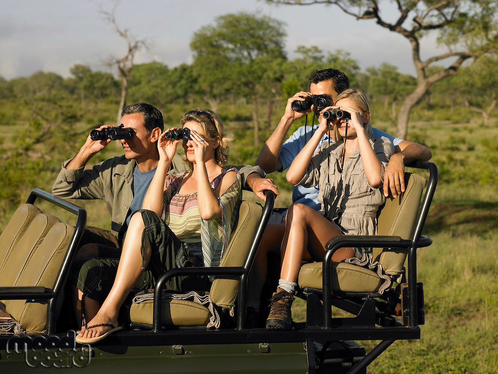 Group of tourists on safari sitting in jeep looking through binoculars