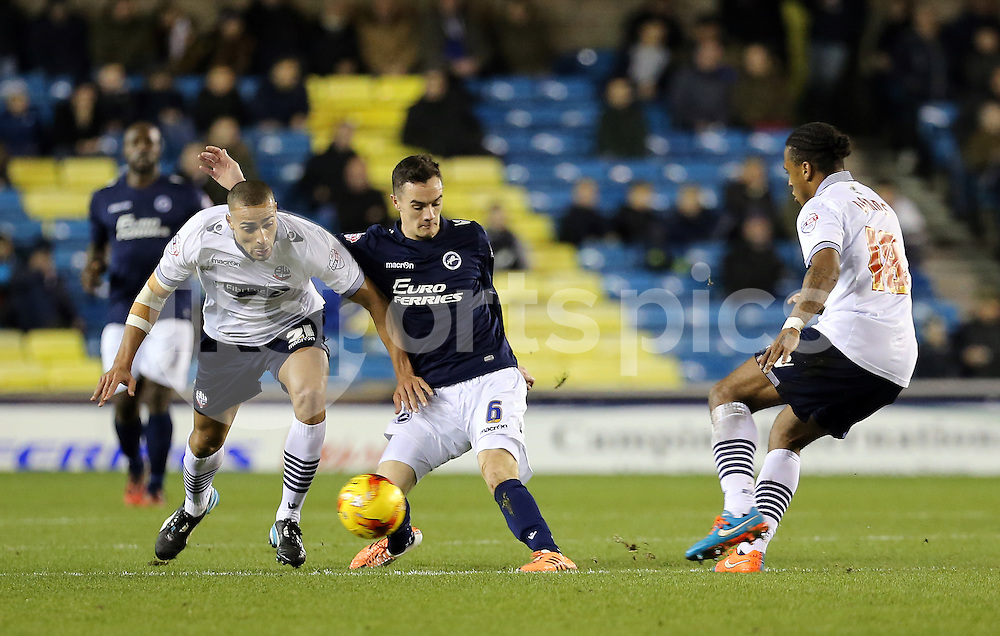 Millwall's Shaun Williams and Bolton's Darren Pratley during the Sky Bet Championship match between Millwall and Bolton Wanderers at The Den, London, England on 19 December 2014. Photo by Dave Peters.