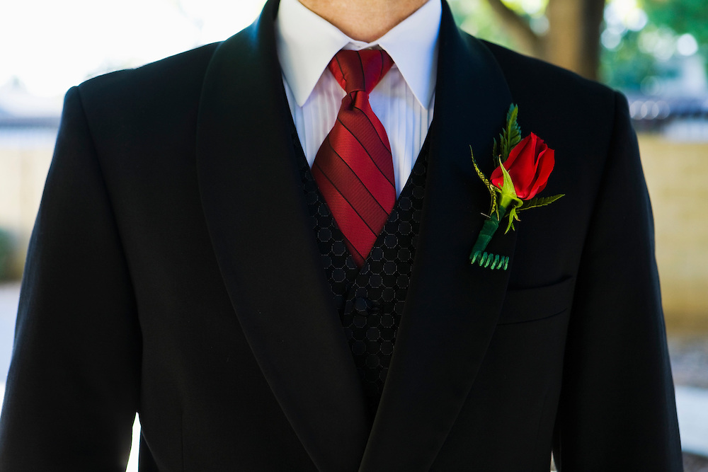 Closeup of a mans suit tie and suit jacket with a rose boutonniere.