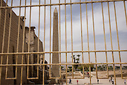 Seen through rusting railings, tourists and the tall Obelisk at the entrance of the ancient Egyptian Luxor Temple, Luxor, Nile Valley, Egypt. The temple was built by Amenhotep III, completed by Tutankhamun then added to by Rameses II. Towards the rear is a granite shrine dedicated to Alexander the Great and in another part, was a Roman encampment. The temple has been in almost continuous use as a place of worship right up to the present day.