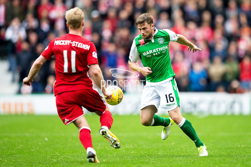 Hibernian defender Lewis Stevenson (#16) controls the ball under pressure from Aberdeen midfielder Gary Mackay-Steven (#11) during the Ladbrokes Scottish Premiership match between Hibernian and Aberdeen at Easter Road, Edinburgh, Scotland on 14 October 2017. Photo by Craig Doyle.