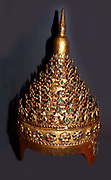 Theatrical Headdress 1800-80  Konbaung period.  Burma. Lacquer, wood and sheet metal, gilded and inlaid with pieces of glass. The high quality of this magnificent headdress suggests it was made at the Burmese court.  It is similar in shape to the crowns worn by royalty, minor deities and Jambupati Buddhas.