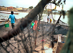 Local Senegalesetraders prepare for the days harvest of fish to be brought  by local fishermen in the town of St. Louis in Senegal.  West Africa has suffered massive overfishing by foreign fishing fleets, with local small fishing boats forced to fish further and further out to sea or to concentrate their activities in sensitive coastal areas.  In the last 45 years, foreign vessels,   caught an estimated 80 percent of the fish taken from West African waters. The coastal nations took home the remaining 20 percent. And their share may get smaller..(Photo by Ami Vitale)