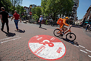 Een bezorger van thuisbezorgd.nl fietst door waar het voetgangersgebied begint. In Utrecht worden fietsers gewezen op een andere route. Vanaf 1 mei mogen fietsers gedurende het grootste deel van de dag niet meer door een deel van het centrum fietsen. Het voetgangersgebied is fors uitgebreid.<br /> <br /> A big painted sign on the road suggest cyclists another route to ride at the city center in Utrecht. A part of the center is closed for cyclists for the main part of the day.
