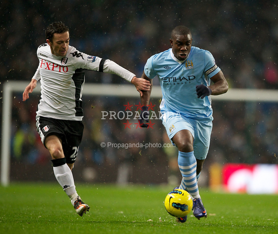LONDON, ENGLAND - Sunday, February 04, 2012: Manchester City's Micah Richards in action against Fulham's Simon Davies during the Premiership match at the Etihad Stadium. (Pic by Chris Brunskill/Propaganda)