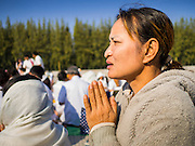"""02 JANUARY 2015 - KHLONG LUANG, PATHUM THANI, THAILAND: A woman prays at Wat Phra Dhammakaya at the start of the 4th annual Dhammachai Dhutanaga (a dhutanga is a """"wandering"""" and translated as pilgrimage). More than 1,100 monks are participating in a 450 kilometer (280 miles) long pilgrimage, which is going through six provinces in central Thailand. The purpose of the pilgrimage is to pay homage to the Buddha, preserve Buddhist culture, welcome the new year, and """"develop virtuous Buddhist youth leaders."""" Wat Phra Dhammakaya is the largest Buddhist temple in Thailand and the center of the Dhammakaya movement, a Buddhist sect founded in the 1970s.   PHOTO BY JACK KURTZ"""