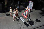 Seen from the top deck of a London bus, three young woman wearing shorts walk past a Man at Work traffic sign on London's edgeware Road.