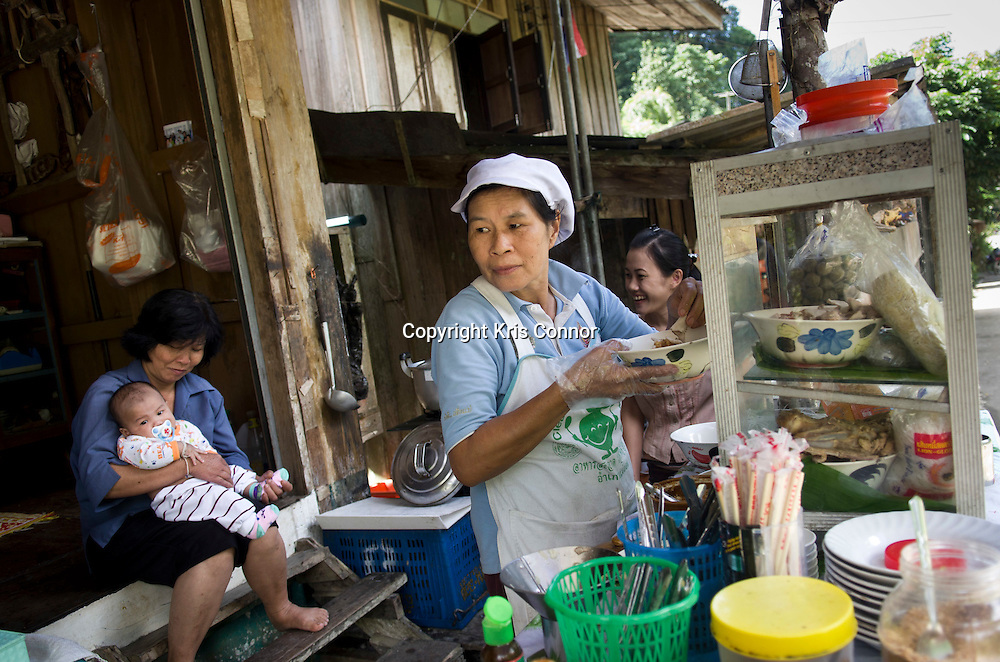 A woman prepares lunch at a small market in a village in the Chiang Mai providence, Thailand. Photo by Kris Connor