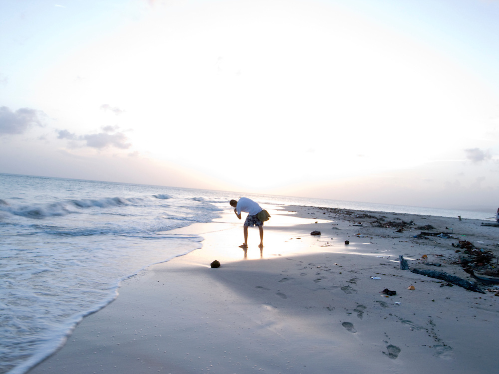 A tourist takes a picture of the sunset at the beach in Port-Salut. Haiti. 6/10/2009 Photo by Ben Depp