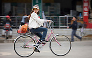 Young woman riding a bicycle in Yangshuo street, China