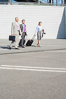 Businesspeople with luggage walking on street