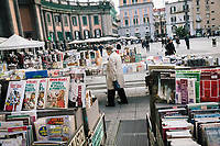 """NAPLES, ITALY - 24 NOVEMBER 2018: An elderly man looks at the book stand in Piazza Sante by the Port'Alba arch in Naples, Italy, on November 24th 2018.<br /> <br /> My Brilliant Friend (Italian: L'amica geniale) is an Italian-American drama television miniseries based on the novel of the same name by Elena Ferrante. The series follows the lives of two perceptive and intelligent girls, Elena (sometimes called """"Lenù"""") Greco and Raffaella (""""Lila"""") Cerullo, from childhood to adulthood and old age, as they try to create lives for themselves amidst the violent and stultifying culture of their home – a poor neighborhood on the outskirts of Naples, Italy. My Brilliant Friend is a co-production between American premium cable network HBO and Italian networks RAI and TIMvision"""