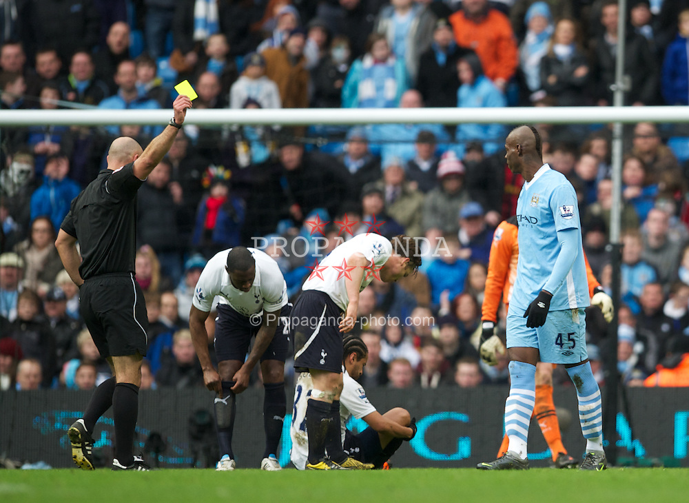 MANCHESTER, ENGLAND - Sunday, January 22, 2011: Manchester City's Mario Balotelli is showen a yellow card by referee Howard Webb against Tottenham Hotspur during the Premiership match at the City of Manchester Stadium. (Pic by David Rawcliffe/Propaganda)
