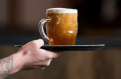 © Licensed to London News Pictures. 04/07/2020. London, UK. A pint of beer is served on a tray at The Ice Wharf pub at Camden Lock, North London as Pubs, bars, cafes and restaurants are allowed to fully open for the first time since lockdown. Photo credit: Ben Cawthra/LNP