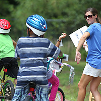 Susan Daughdrill shows the correct way to signal coming to a stop while riding a bicycle as part of the CATCH Kids bike rodeo held Thursday at the Haven Acres Boys & Girls club.