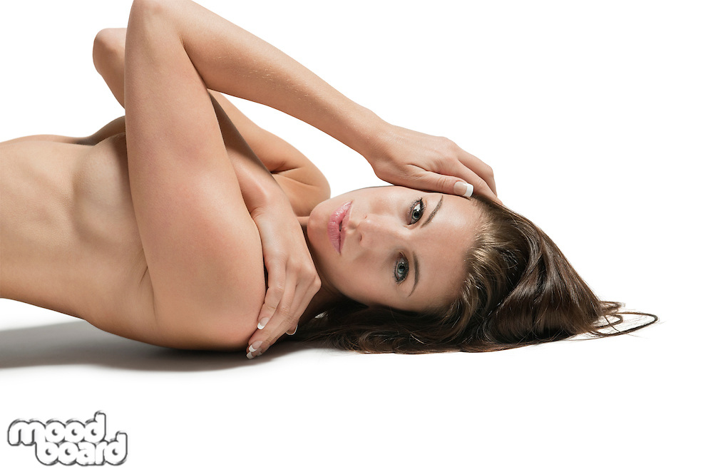 Portrait of a beautiful young woman lying on back over white background