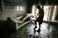 Richard Starr scratchs the muddy floor of his living room in the West End of New Orleans after the flood water recede troughout the city. Katrina Hurricane aftermath in flooded New Orleans. New Orleans, Louisiana. 14 September 2005.