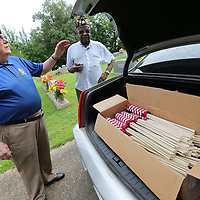 Larry Mims, left, and Clarence Partlow get flags ready for other members of the American Legion Post 49 to put out at cemeteries throughout Lee County on the graves of veterans.