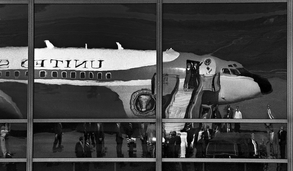 U.S. President Ronald Reagan and his wife Nancy wave from Air Force One reflected in a terminal window after arriving for a visit in Helsinki, Finland. (1988)