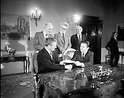 29/03/1976<br /> 03/29/1976<br /> 29 March 1976<br /> Petroleum exploration licences signed at Iveagh House, Dublin. Minister for Industry and Commerce, Mr Justin Keating T.D. and senior oil company executives representing the firms to which licences were being granted signed petroleum exploration licences in respect of exploration offshore of Ireland. Image shows The Minister (seated right) signing the licence with Mr J.W. Rogers, Managing Director Texaco (Ireland) Ltd. on behalf of Texaco Group. Standing behind are Padraig O'Slatarra, Secretary, Dept. of Industry and Commerce; Mr J.C. Holloway, Assistant Secretary, Dept. of Industry and Commerce and possibly Mr D.J. Langan, Texaco (Ireland) Ltd.