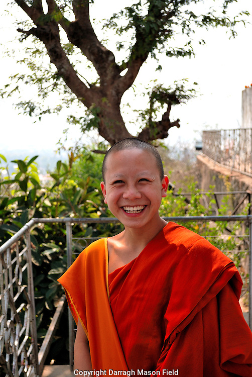 Young smiling novice monk on top of Phu Si hill shrine