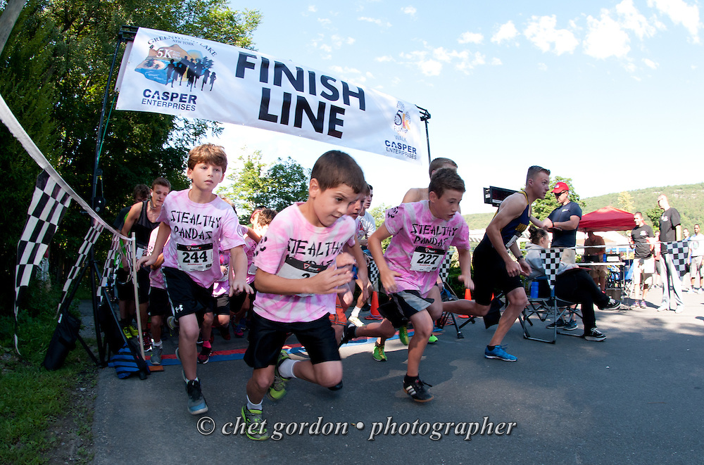 Runners leave the starting line during the Second Annual Greenwood Lake 5K Run in Greenwood lake, NY on Saturday, August 1, 2015. The 5K run followed by a Children's Fun Run is a fundraiser for local families in the village.  © Chet Gordon • Photographer