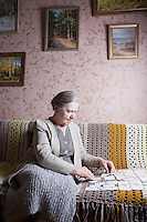 Elderly lady sits playing cards alone