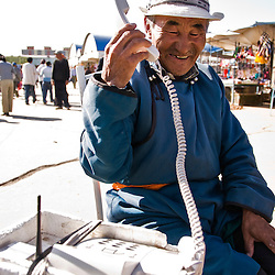 Old Mongolian man, dressed in a traditional way making a phone call, Ulan Bator, Mongolia.