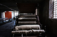 """SOVERIA MANNELLI, ITALY - 17 NOVEMBER 2016: Wool is seen here running through a textile calender machine which polishes the surface of the fabric and makes it smoother and more glossy, in the Lanificio Leo woolen mill in Soveria Mannelli, Italy, on November 17th 2016.<br /> <br /> Lanificio Leo was the first and last machine-operated woolen mill of Calabria, founded in 1873, it employed 50 people until the 1970s, when national policies to develop Italy's South cut out small businesses and encouraged larger productions or employment in the public administration.<br /> <br /> The woolen mill was on stand-by for about two decades, until Emilio Salvatore Leo, 41, started inviting international designers and artists to summer residencies in Soveria Mannelli. With their inspiration, he tried to envision a future for his mill and his town that was not of a museum of the past,<br /> Over the years, Mr. Leo transformed his family's industrial converter of Calabrian wool into a brand that makes design products for home and wear. His century old machines now weave wool from Australia or New Zealand, cashmere from Nepal and cotton from Egypt or South America. He calls it a """"start-up on scrap metals,"""" referring to the dozens of different looms that his family acquired over the years.<br /> <br /> Soveria Mannelli is a mountain-top village in the southern region of Calabria that counts 3,070 inhabitants. The town was a strategic outpost until the 1970s, when the main artery road from Naples area to Italy's south-western tip, Reggio Calabria went through the town. But once the government started building a motorway miles away, it was cut out from the fastest communications and from the most ambitious plans to develop Italy's South. Instead of despairing, residents benefited of the geographical disadvantage to keep away the mafia infiltrations, and started creating solid businesses thanks to its administrative stability, its forward-thinking mayors and a vibrant entrepreneurship nu"""