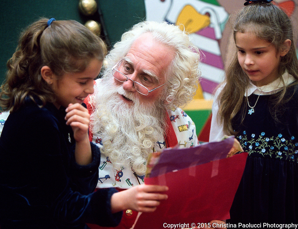 Leah,9, and Rachel,6, Beltz show Santa a collage of gifts they wish to get for Christmas. Parents are John Beltz and Leana Medina-Beltz of Rochester. (Rochester Post-Bulletin,Christina Paolucci)
