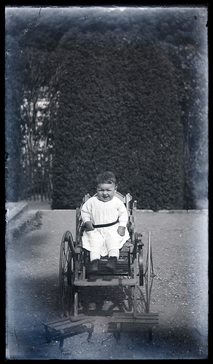 baby toddler outdoors in chair with wheels circa 1920s