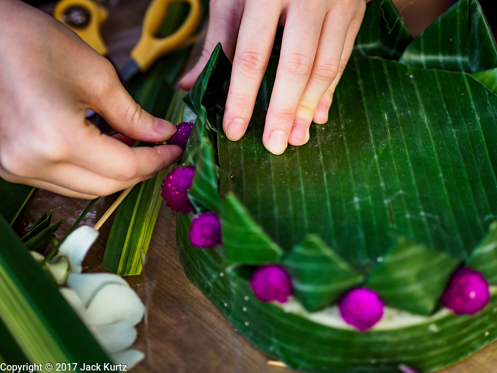 "03 NOVEMBER 2017 - BANGKOK, THAILAND: Young women make krathongs to float in the Chao Phraya River during Loi Krathong at Wat Prayurawongsawat on the Thonburi side of the Chao Phraya River. Loi Krathong is translated as ""to float (Loi) a basket (Krathong)"", and comes from the tradition of making krathong or buoyant, decorated baskets, which are then floated on a river to make merit. On the night of the full moon of the 12th lunar month (usually November), Thais launch their krathong on a river, canal or a pond, making a wish as they do so. Loi Krathong is also celebrated in other Theravada Buddhist countries like Myanmar, where it is called the Tazaungdaing Festival, and Cambodia, where it is called Bon Om Tuk.     PHOTO BY JACK KURTZ"
