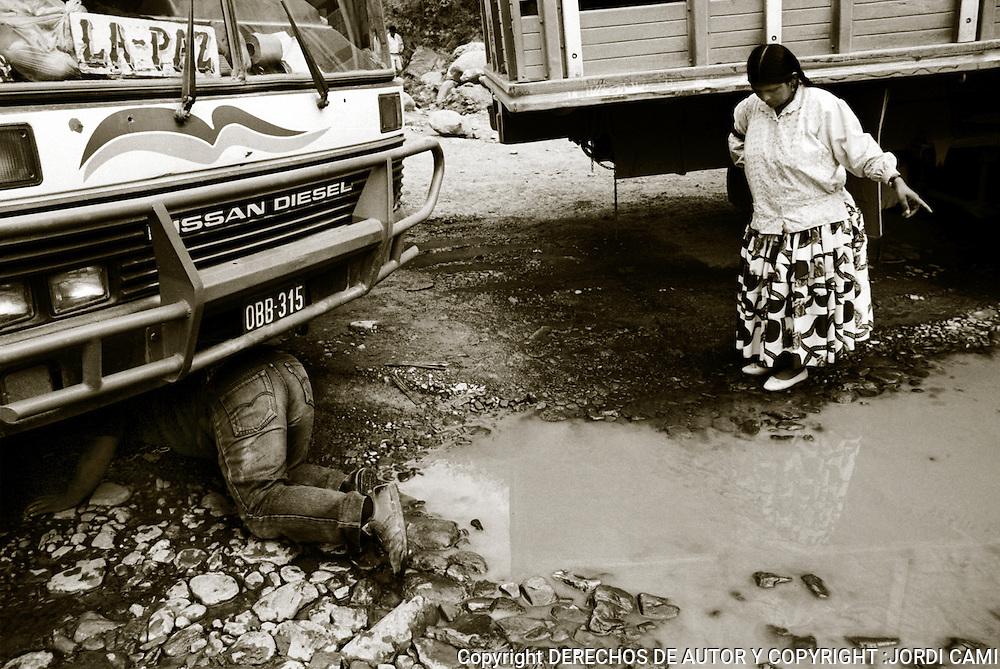 EL AYUDANTE DEL CONDUCTOR DEL AUTOBUS A LA PAZ<br /> REVISA EL VEHICULO EN UNA PARADA. CARRETERA DE LOS YUNGAS .BOLIVIA. FOTO : JORDI CAMI