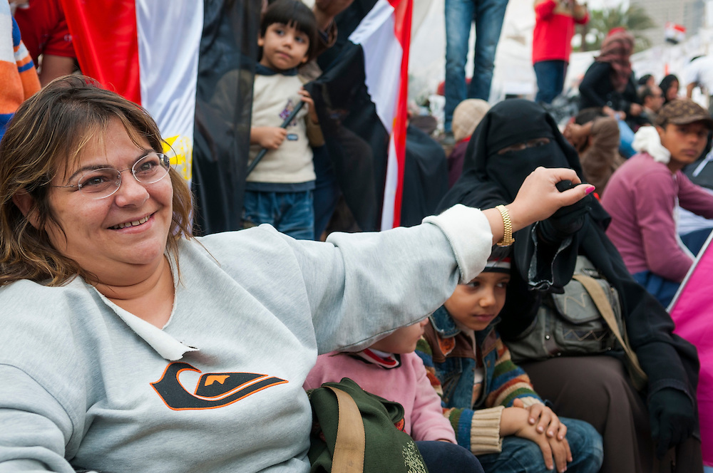 A fully-veiled Muslim woman and a Christian woman grasp hands in a show of solidarity during the anti-Mubarak protest in Tahrir Square. (Cairo, Egypt - February 9, 2011)