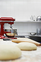 Dough on wooden board beside dough mixer in kitchen