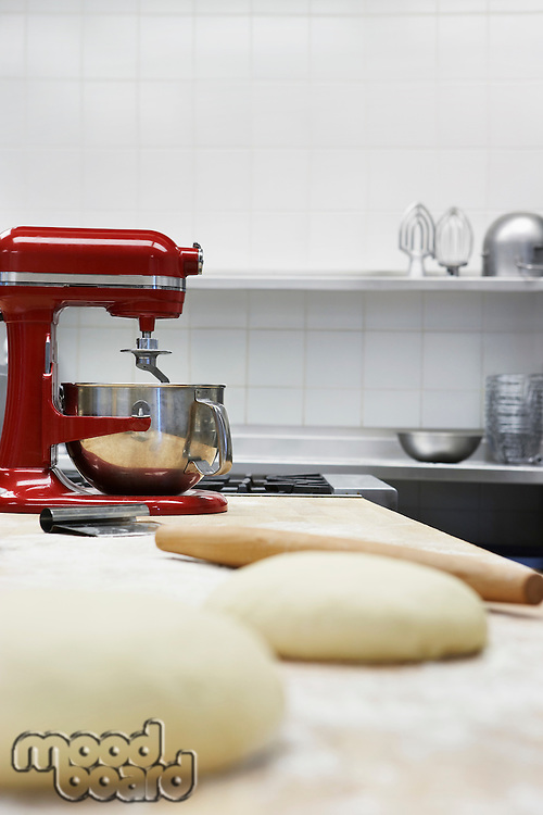 Dough on wooden board beside dough mixer in kitchen